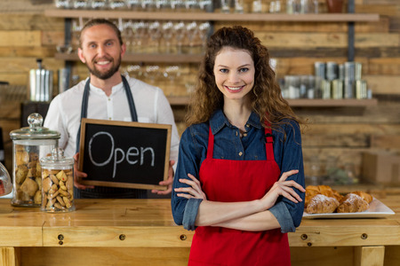 Portrait of waitress standing with arms crossed at counter in café with waiter holding open sign board in background