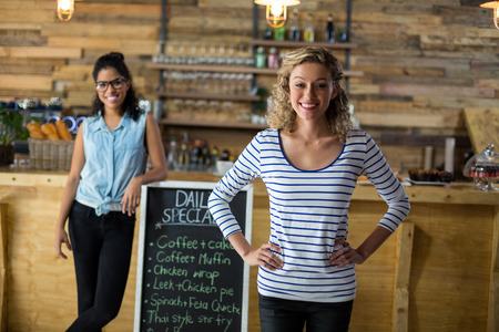 Two female friends standing with menu signboard near counter in café