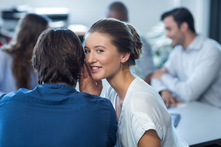 Female business executive whispering to her colleague in office
