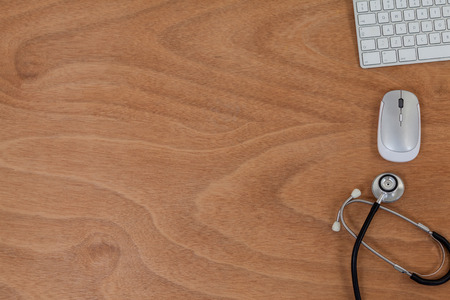 electronic survey: Close-up of stethoscope with keyboard and mouse on table