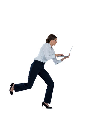 Businesswoman running while using laptop against a white background