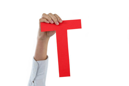 Hand of businesswoman holding alphabet t against white background