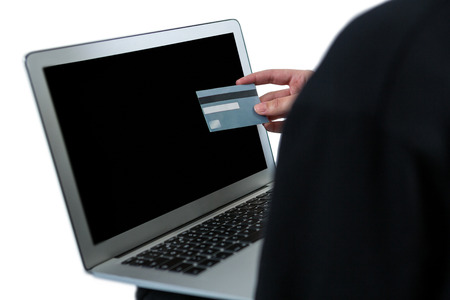 Mid section of hacker using laptop and credit card on white background Stock Photo