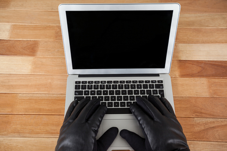 Close-up of hacker using laptop on white background Stock Photo