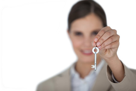 classy house: Close-up of businesswoman showing new house key on white background