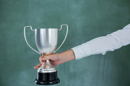Hand of businesswoman holding trophy against green background