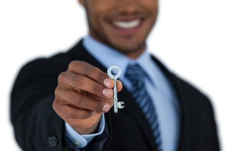 classy house: Businessman showing new house key on white background Stock Photo