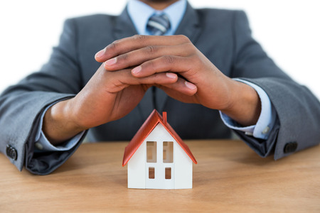 classy house: Mid section of businessman protecting house model and car with hands