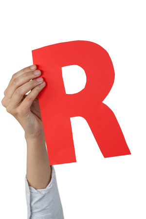 Close-up of businesswoman holding alphabet r against white background