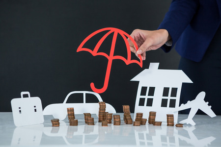 classy house: Conceptual image of businesswoman protecting her wealth with umbrella Stock Photo
