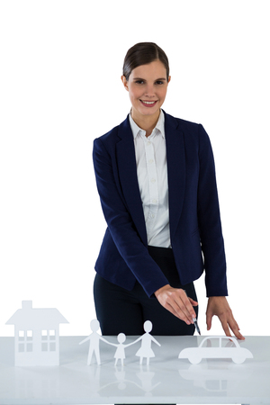 Portrait of smiling businesswoman pointing on a paper cut out of family, car and house against white background