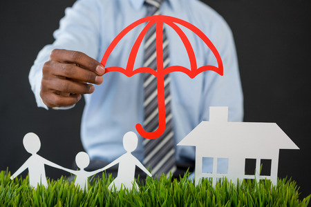 Mid section of businessman protecting paper cut out family, house and car with umbrella