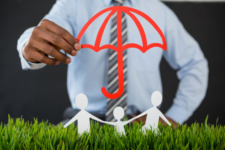 Mid section of businessman protecting paper cut out family with umbrella Stock Photo