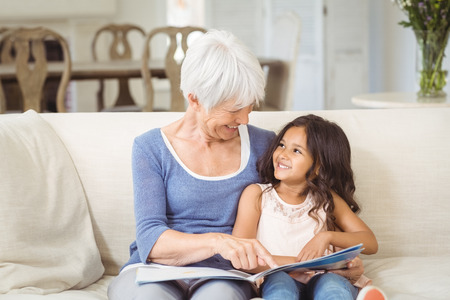 Grandmother and granddaughter interacting while looking at photo album in living room at home