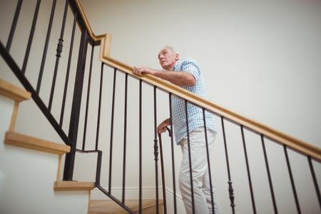 年配の男性が杖を自宅の 2 階を登る