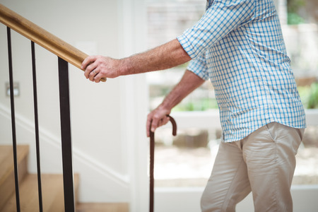 Mid section of senior man climbing upstairs with walking stick at home