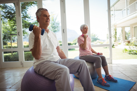 ageing process: Senior couple exercising with dumbbells on exercise ball at home