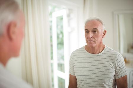 Senior man looking at mirror in bathroom