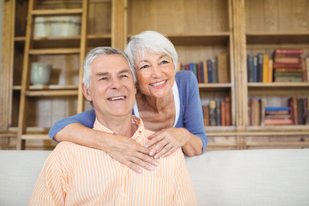 Smiling senior woman embracing a man in living room at home