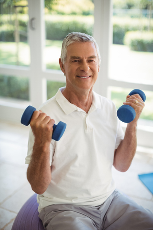 Happy senior man exercising with dumbells at home