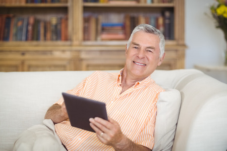 Portrait of smiling senior man using digital tablet in living room at home Stock Photo
