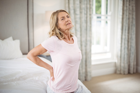 Senior woman having back pain in bedroom at home