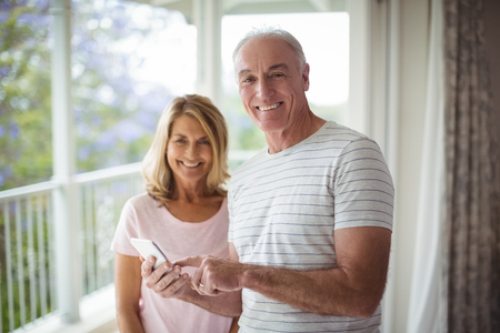 Portrait of happy senior couple standing in balcony with mobile phone at home Stockfoto