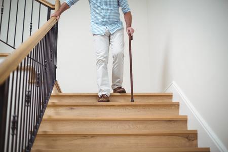 집에서 막대기를 걷고 계단을 올라가는 시니어 남자 스톡 콘텐츠