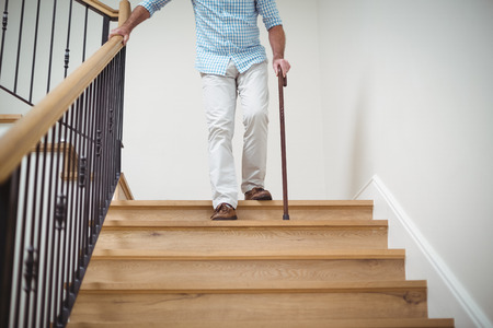 Senior man klimmen beneden met wandelstok thuis