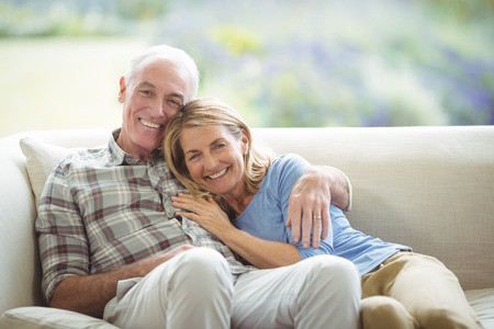 Portrait of smiling senior couple sitting together on sofa in living room at home Stock Photo