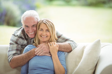 Portrait of smiling senior man embracing a woman in living room at home