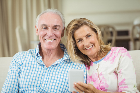 Portrait of smiling senior couple sitting on sofa with laptop in living room