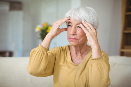 Senior woman suffering from head ache in living room at home Stock Photo