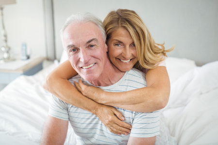 Portrait of happy senior couple embracing each other on bed in bedroom