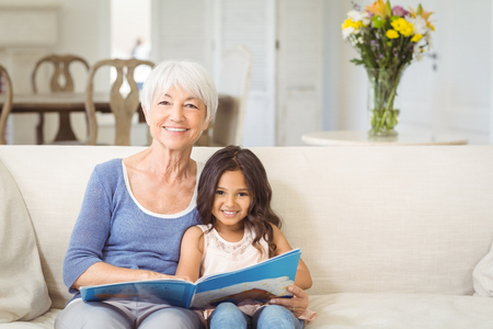 Portrait of smiling grandmother and granddaughter sitting together on sofa with photo album Stock Photo
