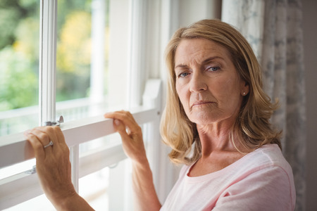 Portrait of senior woman standing next to window at home Stock Photo