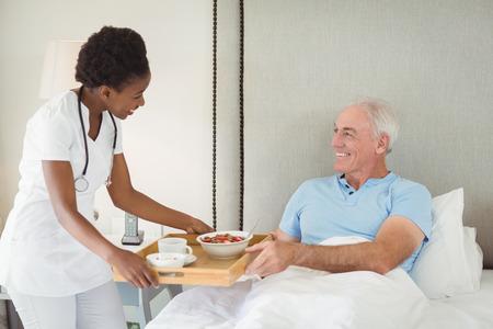 Nurse serving breakfast to senior patient in bedroom