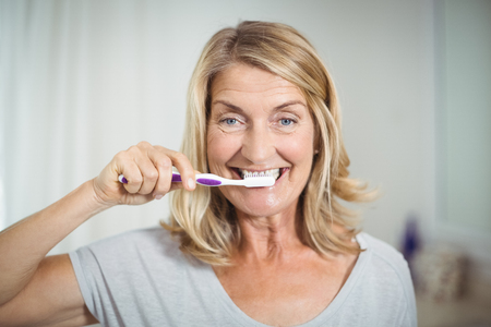 domicile: Portrait of senior woman brushing her teeth in bathroom at home