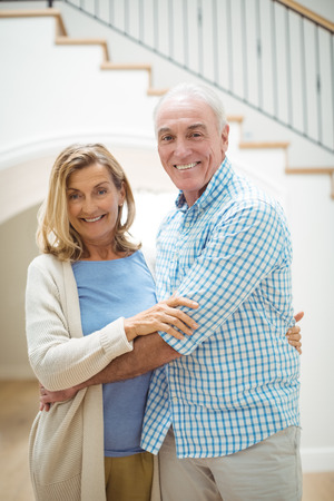 Portrait of smiling senior couple embracing each other in living room at home