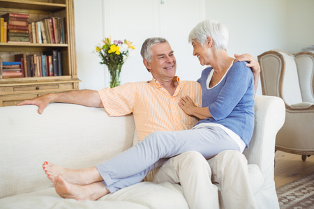 romance strategies: Smiling senior woman sitting on mans lap in living room at home Stock Photo