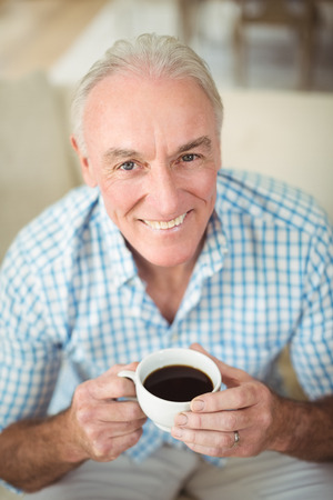 Portrait of smiling senior man having cup of coffee in living room at home
