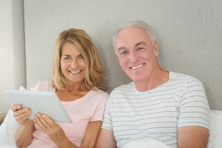 Portrait of smiling couple using digital tablet on bed in bedroom Stock Photo