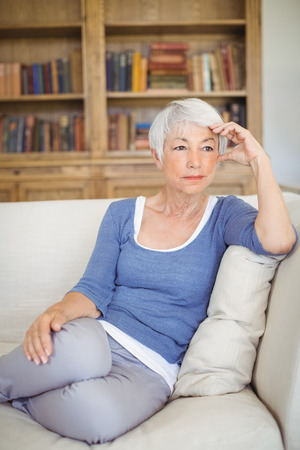ageing process: Thoughtful senior woman sitting on sofa in living room at home