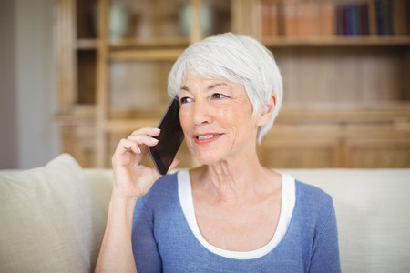 Smiling senior woman talking on mobile phone in living room at home