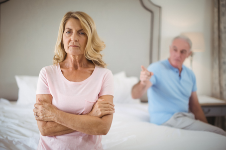 ageing process: Upset senior couple arguing in bedroom at home