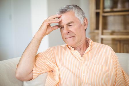 Tense senior man sitting on sofa in living room at home