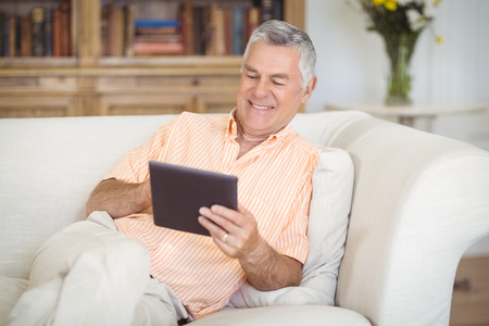 Smiling senior man using digital tablet in living room at home