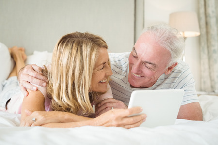 Smiling couple lying on bed and using laptop in bed room