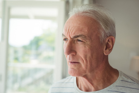 ageing process: Thoughtful senior man standing next to window at home Stock Photo