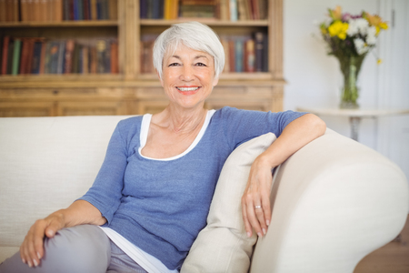 Portrait of smiling senior woman sitting on sofa in living room at home